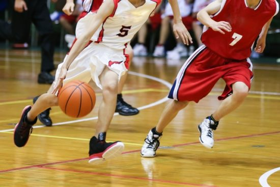 バスケットボールをしている男子学生