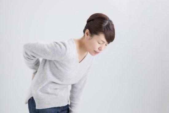 腰を痛がる中年女性