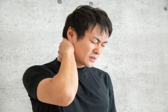 首を痛がる男性