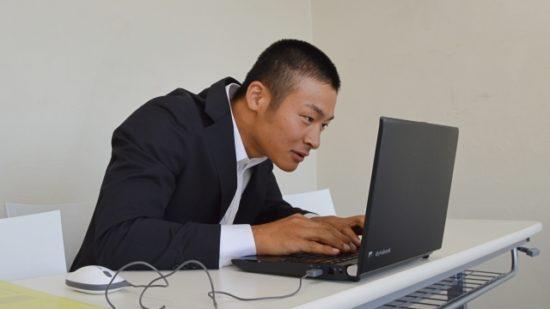 パソコンをしている猫背の男性